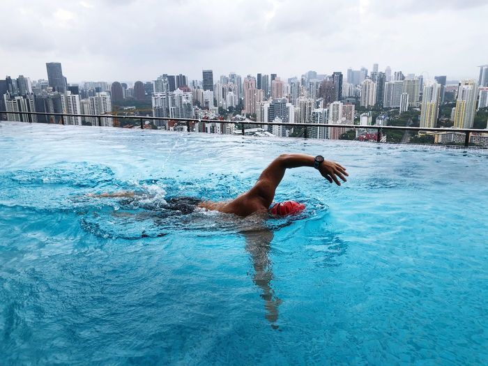 Man Swimming In Infinity Pool Against Cityscape