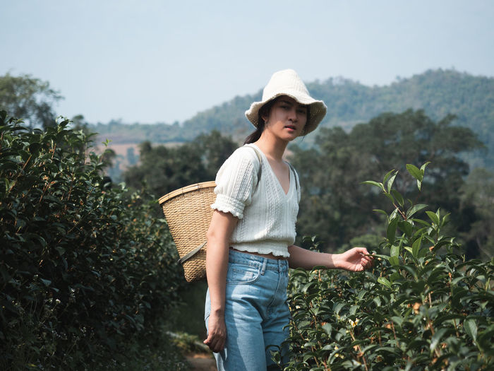 Full length of young woman standing in farm