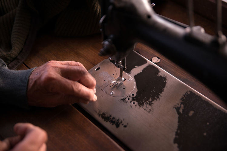 Close-up of person hands working on sewing machine