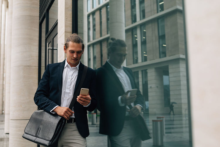 Smiling businessman using smart phone while standing by building
