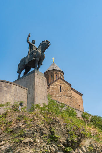 Low angle view of statue against historic building against clear blue sky