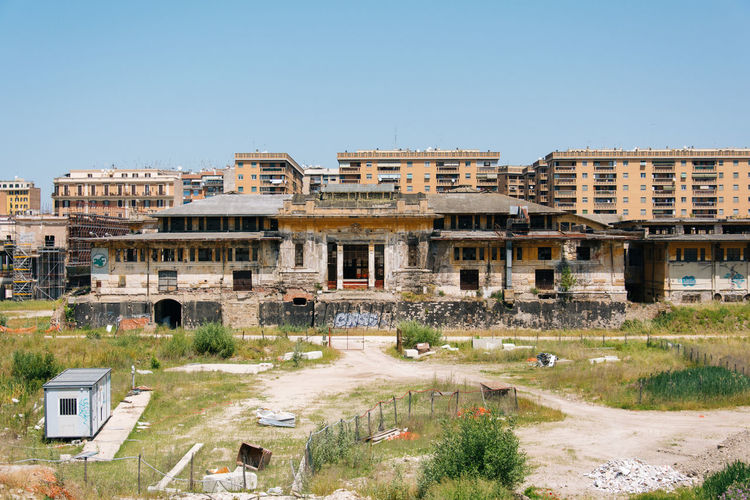 Field By Old Buildings In Circus Maximus Against Clear Sky