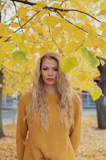 Portrait of young woman standing against autumn tree