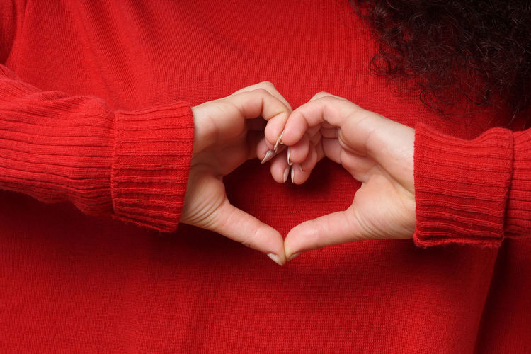 Midsection Of Woman Making Heart Shape Through Hands