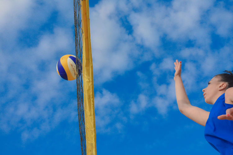 Low angle view of woman playing volleyball