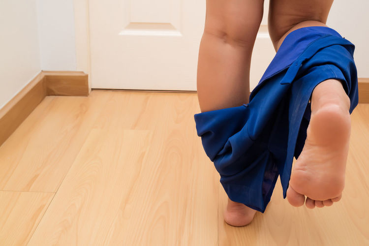 Low section of woman undressing on hardwood floor at home