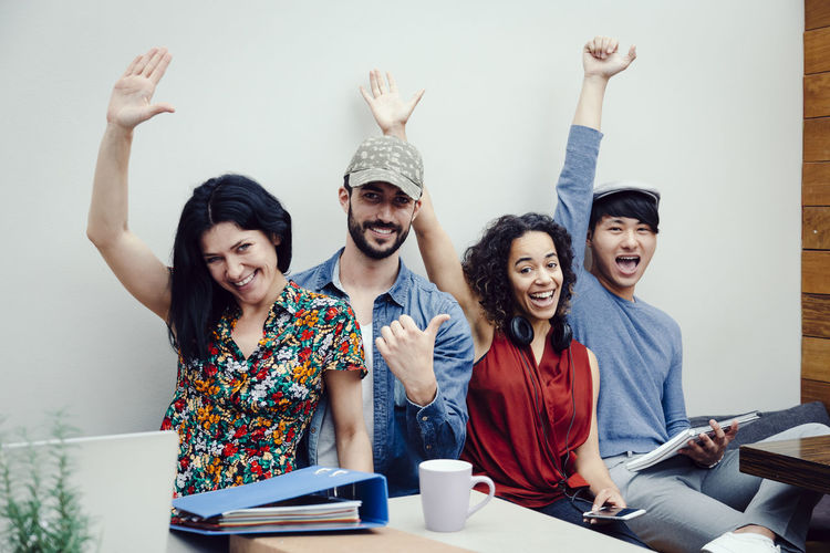Portrait Of Cheerful Creative Business People With Hands Raised Sitting Against White Wall