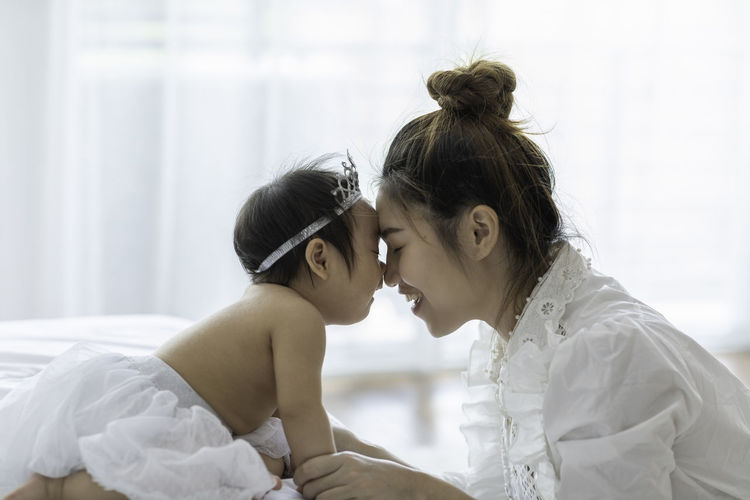 Side view of mother and daughter at home