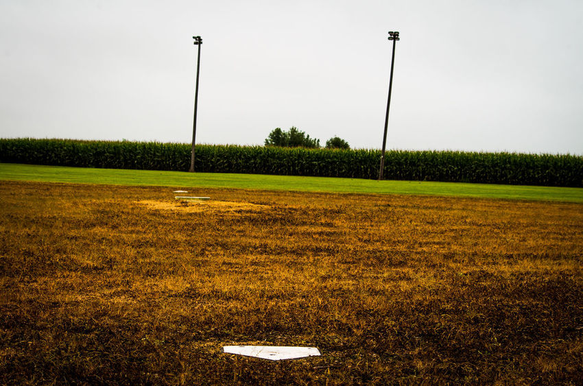 Field Of Dreams Absence Baseball Diamond Beauty In Nature Day Environment Field Grass Green Color Land Landscape Nature No People Outdoors Plant Sky Sport Street Street Light Tranquil Scene Tranquility Tree