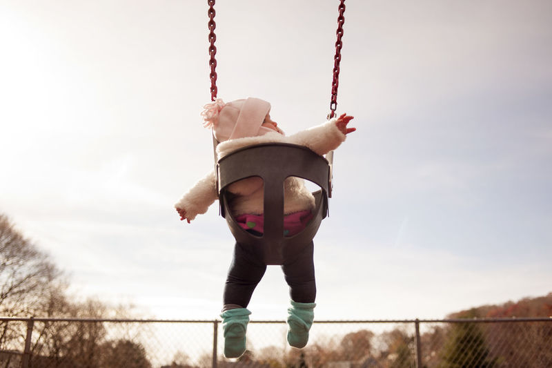 Low angle view of boy climbing on rope against sky