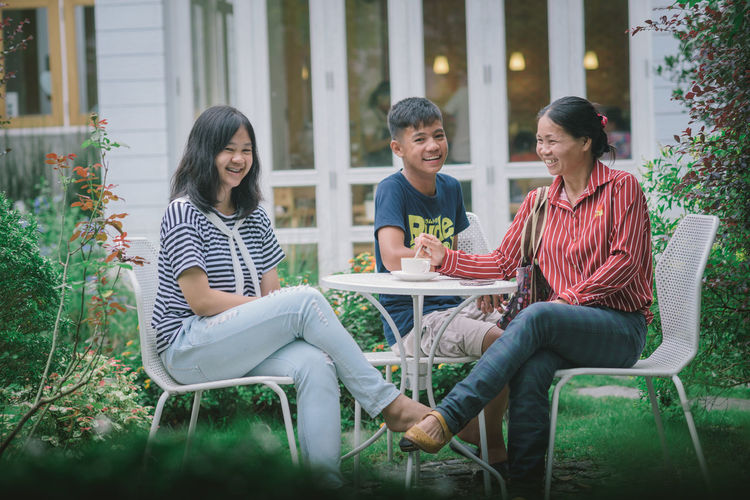Women sitting on chair at plants