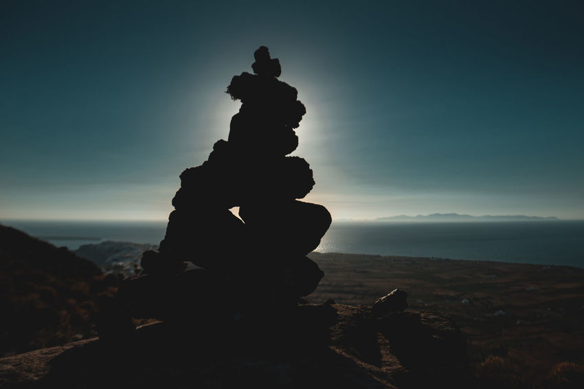 Greece Freedom Island Life Rock Pile Silhouette Traveling Dark Colors Destination Europe Glare Of The Sun Greece Greek Island Holiday Destination Horizon Island Landscape Ocean Outdoors Pile Of Stones Piled Up Rock - Object Santorini Stack Sunglare Tranquil Scene Vacation