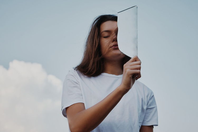 Low Angle View Of Young Woman Holding Mirror Against Sky