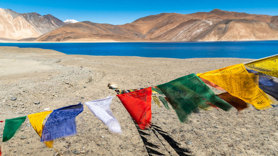 Clothes drying on beach against mountains
