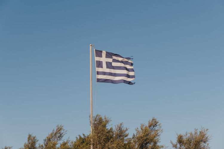 Greek flag in the wind, against blue sky, selective focus.