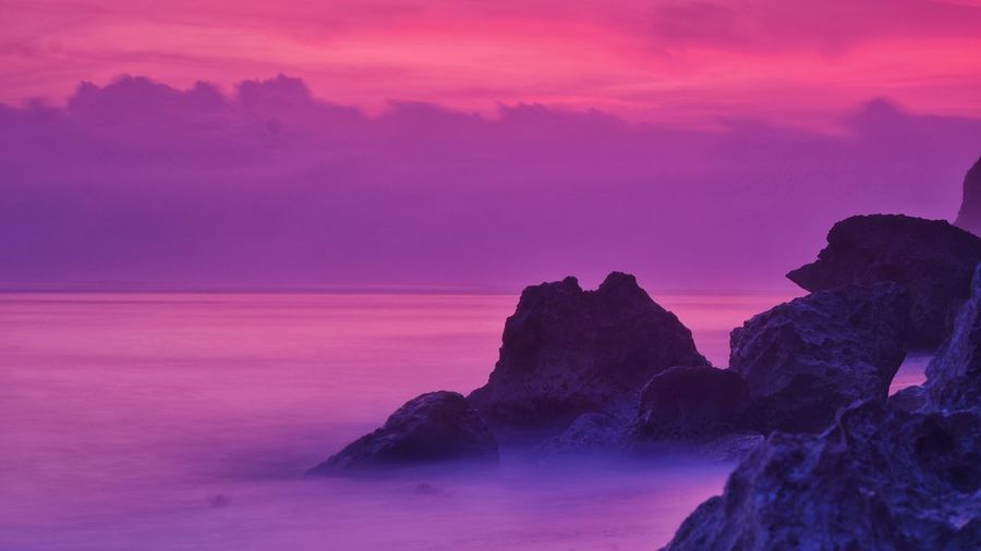 Rock formation on sea against romantic sky at sunset