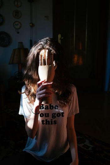 Young Woman Hiding Face With Wooden Hand At Home