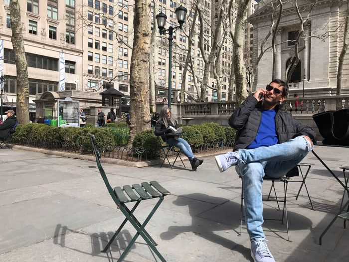 Man talking on phone while sitting on chair in city