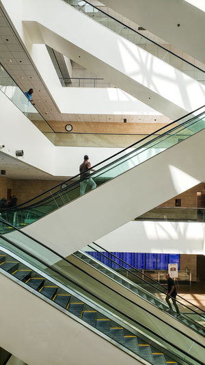 In full color. Working Full Length Modern Occupation Men Business Finance And Industry Architecture Escalator Moving Walkway  Elevated Walkway Hand Rail Steps Steps And Staircases