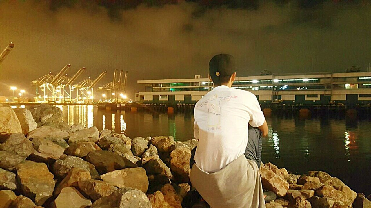 night, water, rear view, men, real people, built structure, river, architecture, building exterior, occupation, outdoors, one person, lifestyles, city, illuminated, harbor, working, nature, one man only, only men, sky, adult, adults only, people