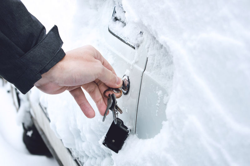 Cropped image of hand opening car door with key