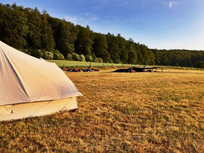 Camping tent on field against sky