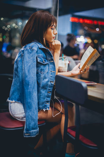 Beautiful Woman Casual Clothing City Denim Jacket Fashion Full Length Illuminated Indoors  Leisure Activity Lifestyles Night One Person People Real People Side View Sitting Technology Touch Screen Wireless Technology Women Young Adult Young Women Modern Workplace Culture