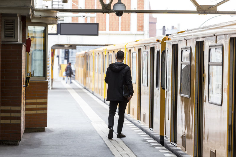 Rear View Full Length Of Man Walking By Train At Railroad Station