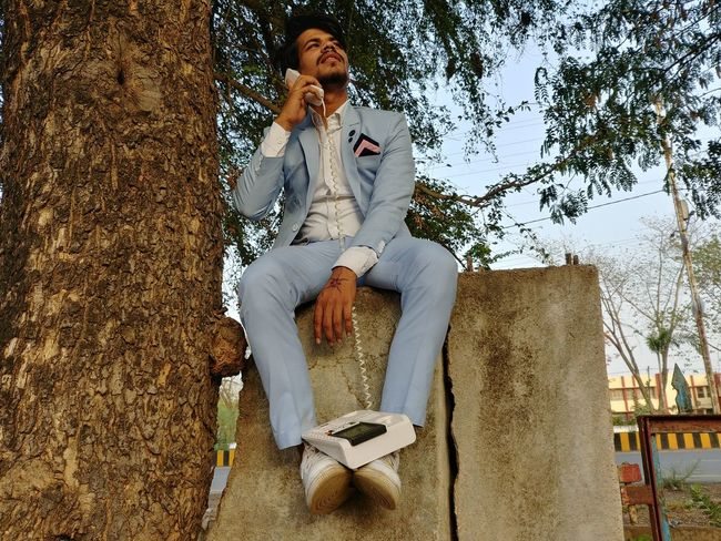 Style Style And Fashion Attitude Pose Man Swag Sitting One Person Full Length Casual Clothing Real People Day Leisure Activity Smart Phone Tree Front View Nature Lifestyles Technology Men Outdoors