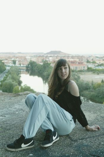 Young Woman Sitting On Concrete Wall By River Against Clear Sky
