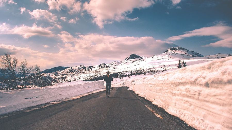 Rear View Of Man Standing On Road By Snowcapped Mountains Against Sky