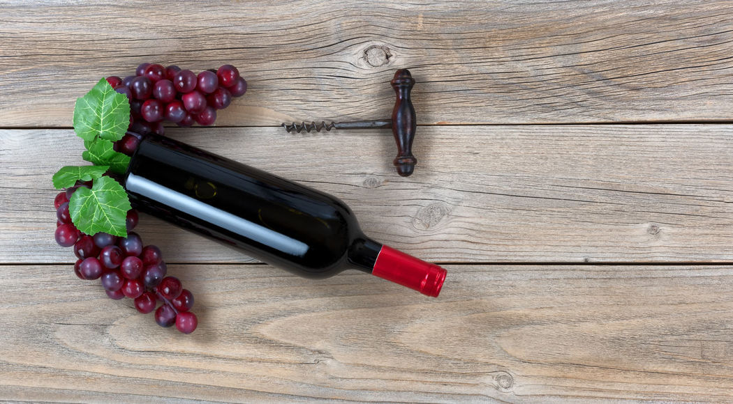 Overhead view of Red wine bottle with grapes and corkscrew on weathered wooden boards Celebration Copy Space Merlot Red Wine Rustic Wood Alcohol Anniversary Bottle Corkscrew Drink Food Food And Drink Fruit Grape Healthy Eating High Angle View Overhead View Red Wine Wine Grapes