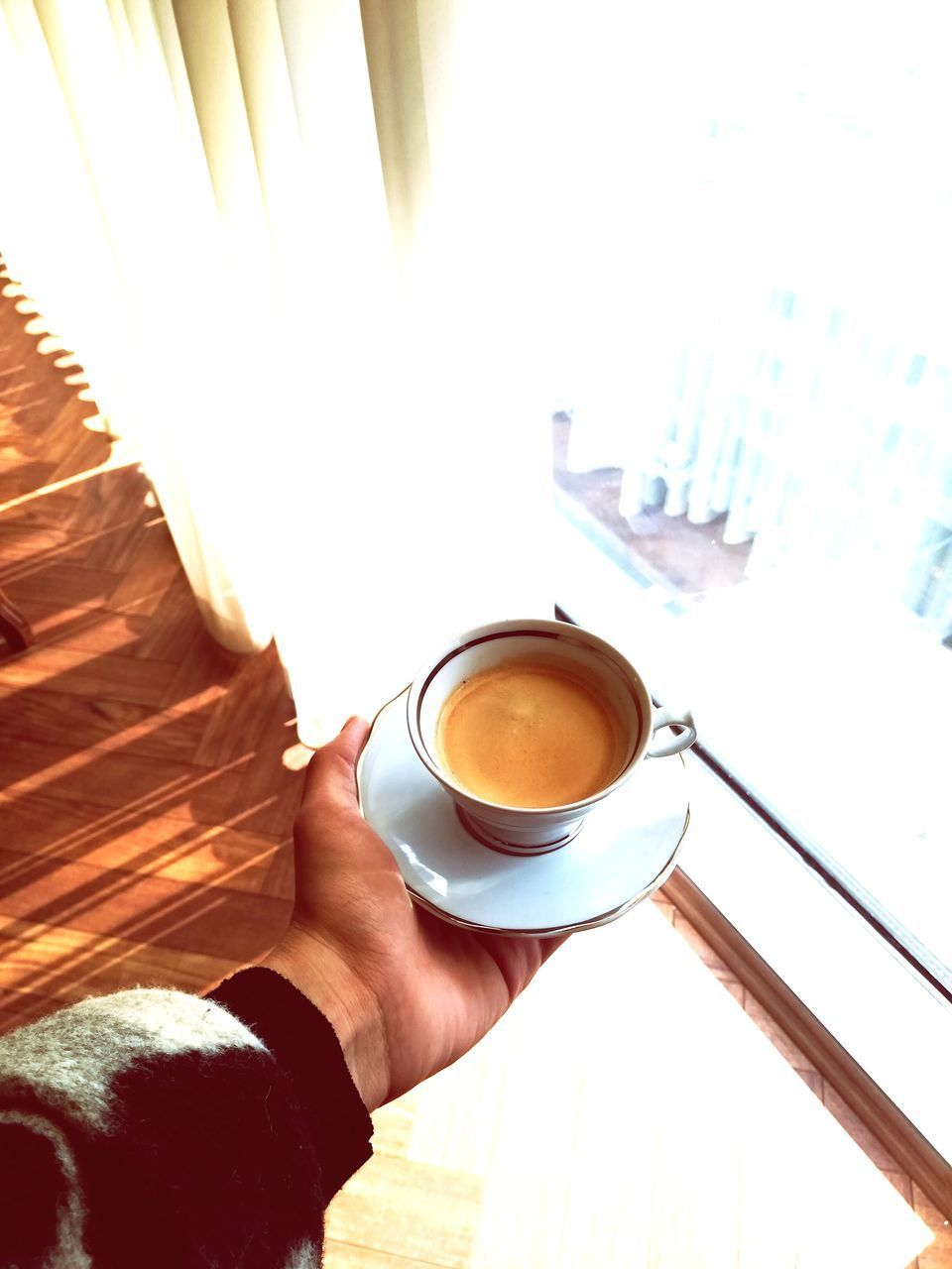 CROPPED IMAGE OF HAND HOLDING COFFEE WITH CUP OF CAPPUCCINO