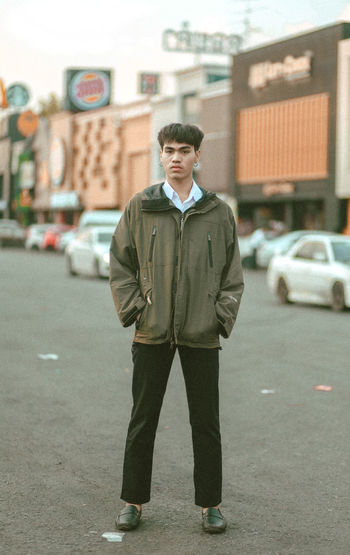 Portrait of young man standing on street in city