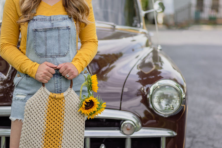 Midsection of woman holding yellow while standing by car