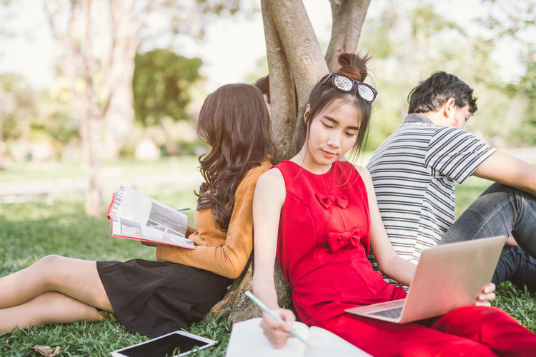 Young friends studying at park