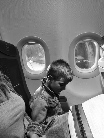 Side view of boy sitting by airplane window