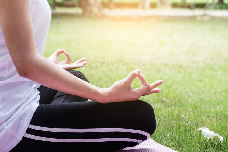 Low section of woman doing yoga at park