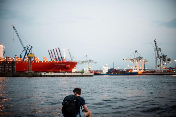 Rear view of man sitting at harbor