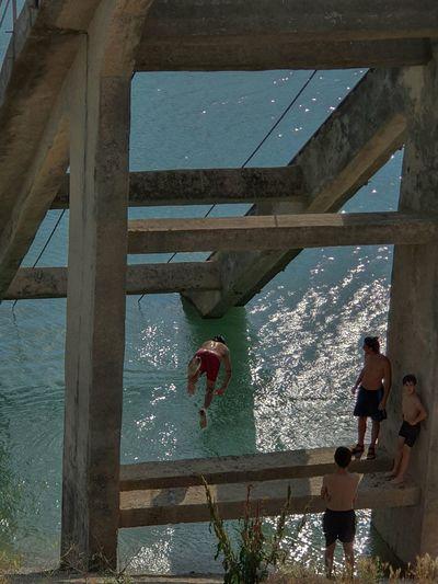 People on bridge over sea