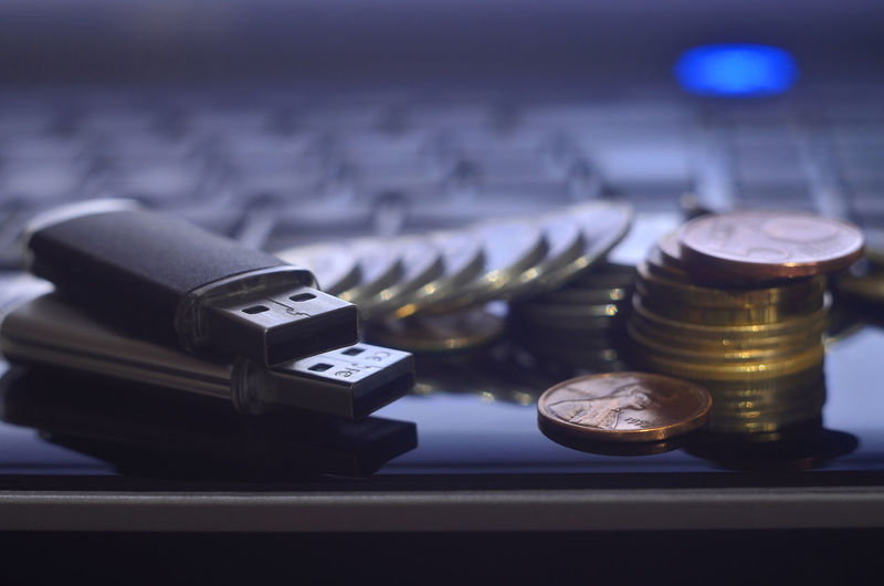 Close-up of usb sticks and coins on laptop