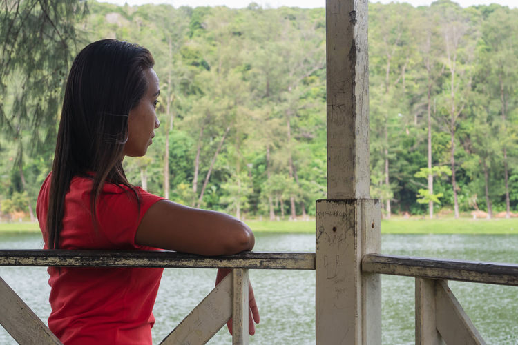 Side view of young woman looking at railing
