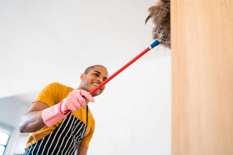 Young man cleaning furniture with broom while standing on stool at home