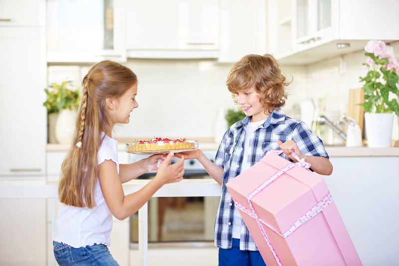 Siblings Packing Cake In Gift Box At Home
