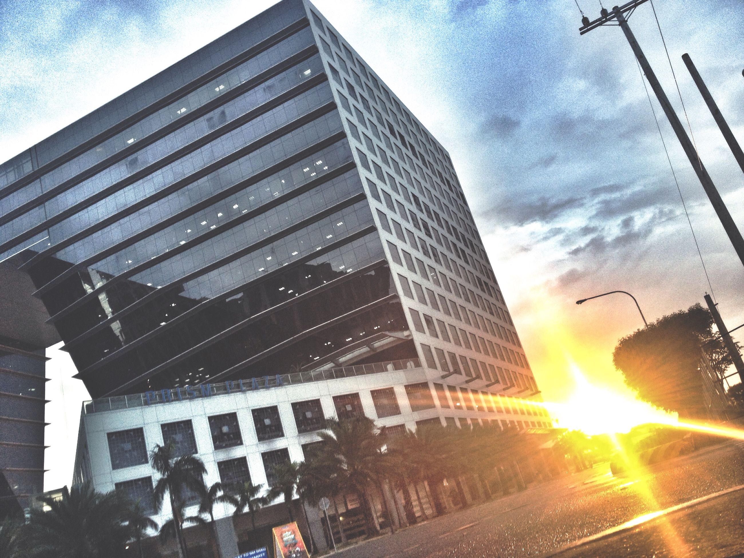 architecture, building exterior, built structure, city, sky, low angle view, modern, sun, office building, sunbeam, skyscraper, sunlight, cloud - sky, tall - high, building, lens flare, city life, tower, sunset, reflection