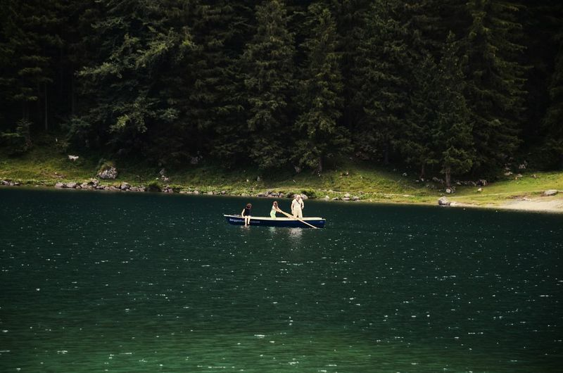 People on lake against trees in forest