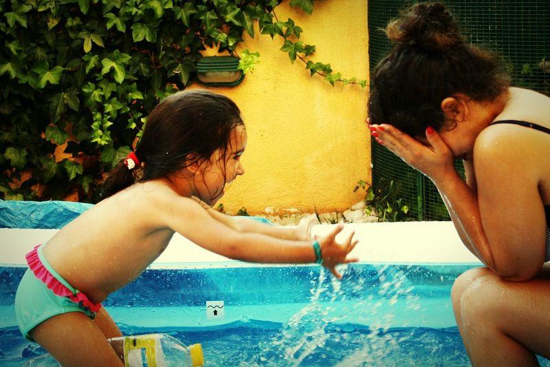 Siblings playing in swimming pool