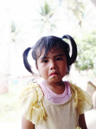 Little girl wears lipstick, frowning and upset