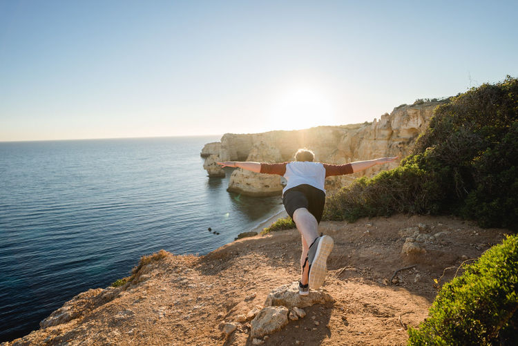 Rear View Of Playful Man On Cliff By Sea Against Clear Sky