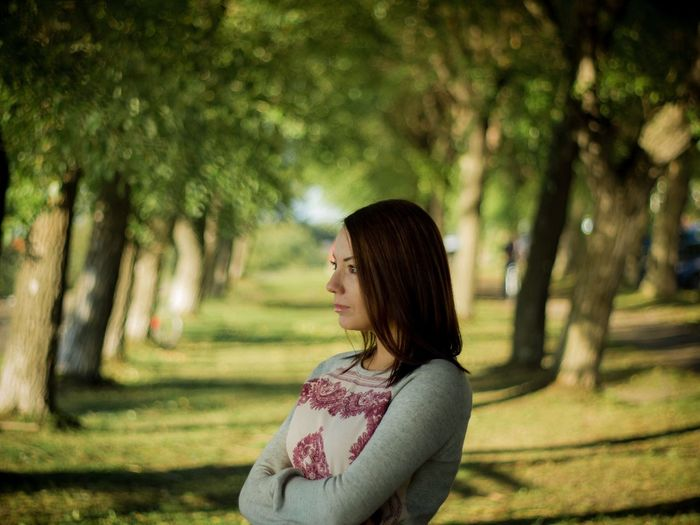 Thoughtful woman with arms crossed standing on pathway amidst trees at park